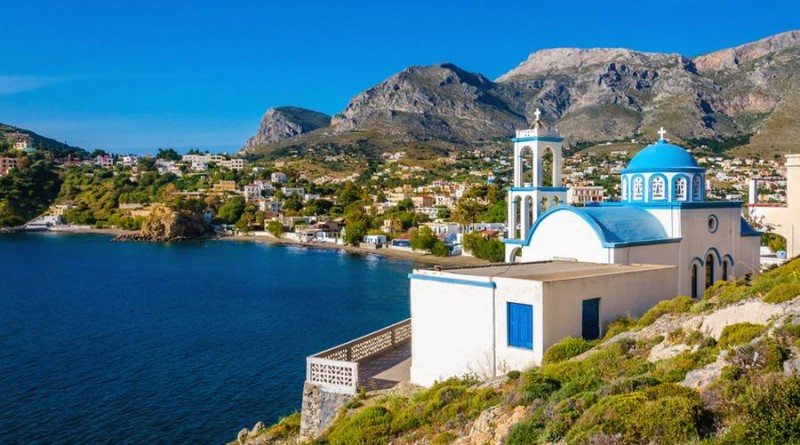 Typical for Greece white church with azure-blue dome with peacful bay in the background on Kalymnos Island, Greece
