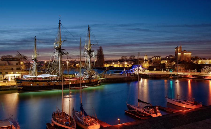 Photographie de la Frégate Hermione et de bateaux de nuit, vue de côté