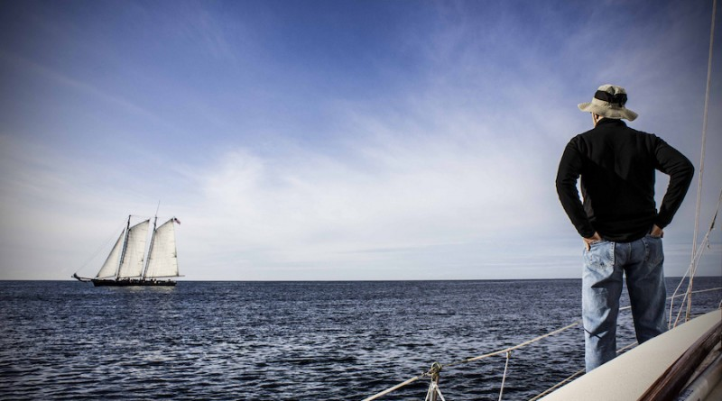 Photographie d'un skippeur sur son voilier, vue de dos