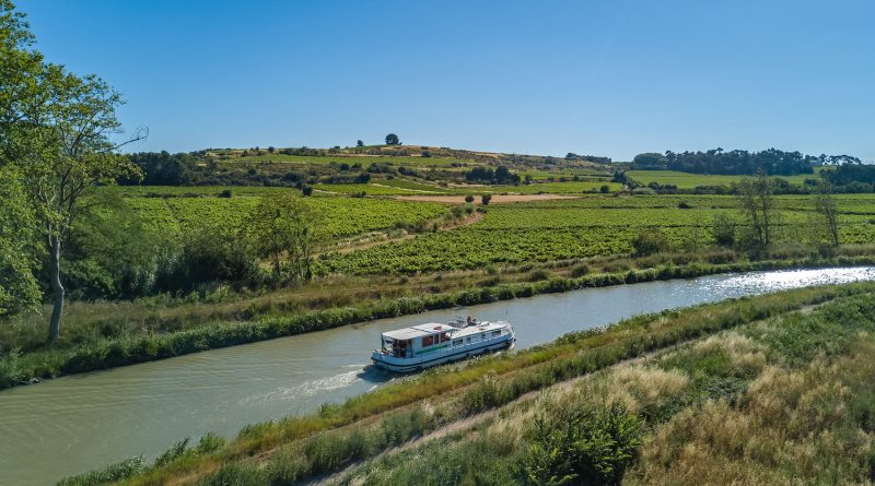 Aerial top view of boat in Canal du Midi from above, family travel by barge and vacation in Southern France
